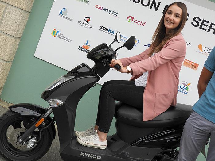 Jeune fille présentant les scooters mis à disposition des habitants dans le cadre du pass mobilité en Bretagne romantique