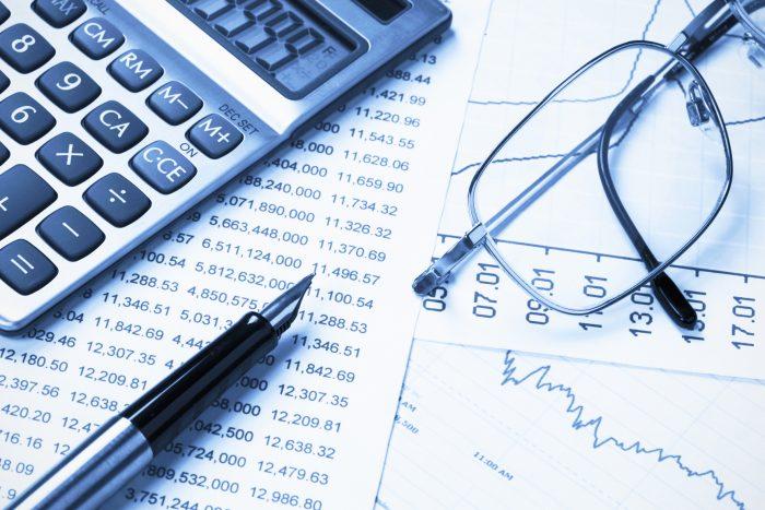 calculatrice, stylo et lunettes sur fiches de budgets