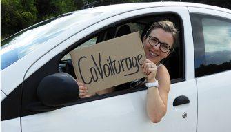 jeune femme assise dans une voiture blanche tenant un panneau co-voiturage