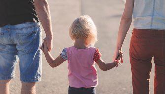une petite fille blonde avec un jean et un t-shirt rose tient la main de son papa et de sa maman