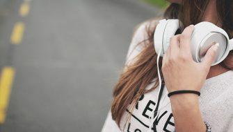jeune fille portant un sxeat blanc et un casque audio autour du cou