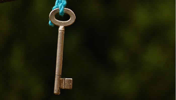 clé en cuivre suspendue à une ficelle bleue