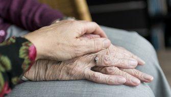main posée sur les mains d'une personne âgée
