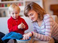 Jeune fille jouant avec un enfant portant un pull rouge dans le salon